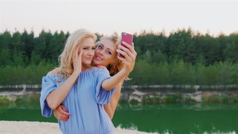 Two-Attractive-Women-In-Dresses-Make-Selfie-On-The-Background-Of-The-Picturesque-Lakes-And-Forests-S