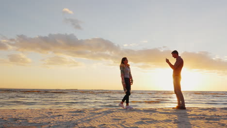A-Young-Couple-Is-Photographed-By-The-Sea-At-Sunset-Man-Photographing-His-Girlfriend-Phone-Prores-Hq