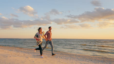 Young-Couple-Running-Along-The-Seashore-At-Sunset-The-Concept---A-Happy-Honeymoon-The-Energy-Of-Yout