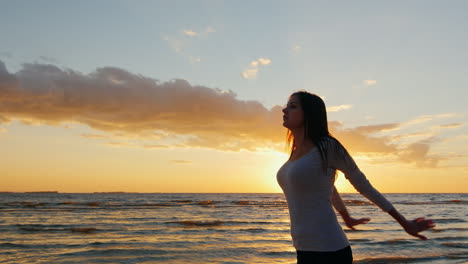 Young-Woman-With-A-Beautiful-Figure-Warming-Up-Before-An-Evening-Jog-On-The-Beach-At-Sunset