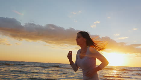 Young-Sports-Girl-Runs-With-A-Good-Figure-On-The-Beach-At-Sunset-Beautiful-Hair-Fluttering-In-The-Wi
