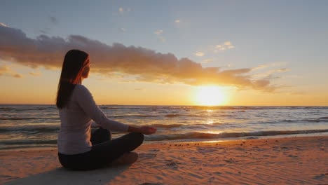 Young-Woman-With-Long-Hair-Sitting-On-The-Beach-At-Sunset-Meditating-Calm-Self-Confidence-And-Health