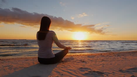 No-Stress-Calm-Young-Woman-Sitting-In-A-Lotus-Position-On-The-Beach-At-Sunset