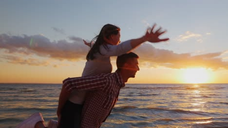 Young-Couple-In-Love-Having-Fun-On-The-Beach-At-Sunset-Berugi-A-Girl-Sits-On-The-Shoulders-Of-Men-Ru