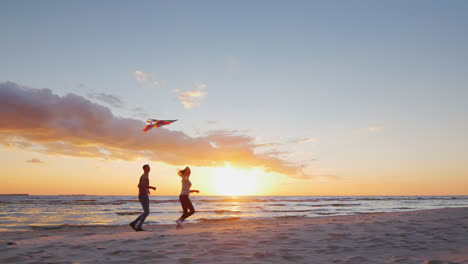 Young-Couple-Playing-With-A-Kite-On-The-Beach-At-Sunset