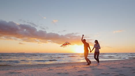 Young-Couple-Playing-With-A-Kite-On-The-Beach-At-Sunset-Prores-Hq-10-Bit-Video