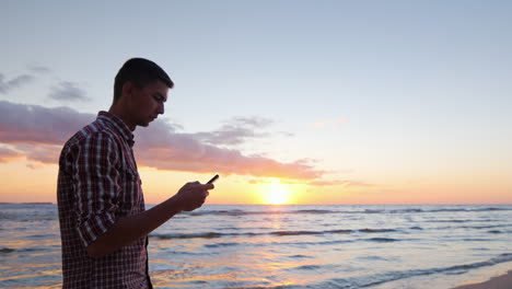 Young-Lonely-Man-Walking-Along-Seashore-At-Sunset-Typing-On-Phone