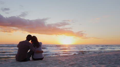 A-Young-Couple-Admiring-The-Sunset-At-Sea-Sit-In-An-Embrace-On-The-Sand-Prores-Hq-10-Bit-Video