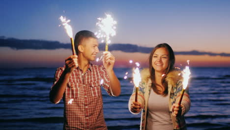 Young-Couple-Having-Fun-With-Fireworks-In-The-Hands-Fireworks-Lit-The-Pair-Laughing-Having-A-Good-Ti