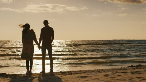 Silhouettes-Of-Young-Couple-Admiring-The-Sunset-On-The-Sea-Embracing-Cool-Day-The-Wind-Blows