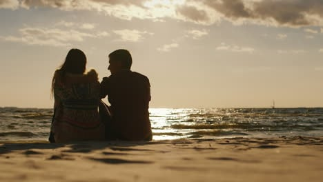 Silhouettes-Of-Couples-In-Love-Sitting-On-The-Beach-Watching-The-Sunset-And-A-Board-With-A-Sail-Back