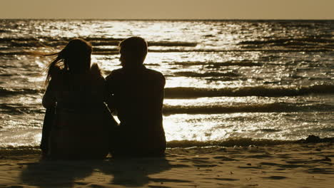 Silhouettes-Of-Couples-In-Love-Sitting-On-A-Background-Of-The-Sea-Which-Reflects-The-Setting-Sun-Rea
