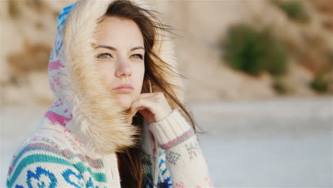 Thoughtful-Young-Woman-Sitting-On-The-Beach-The-Wind-Blowing-In-Her-Face-Cool-Day-Time-To-Dream
