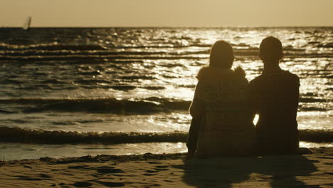A-Loving-Couple-Sitting-Together-On-The-Sand-Admiring-The-Sea-And-The-Sunset-Sea-Swimming-Windsurfer