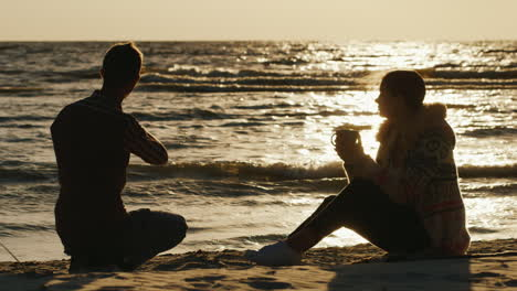 Romantic-Young-Couple-Relaxing-On-The-Beach-Or-A-Lake-On-A-Cool-Day-Woman-Drinking-Tea-From-A-Cup-A-