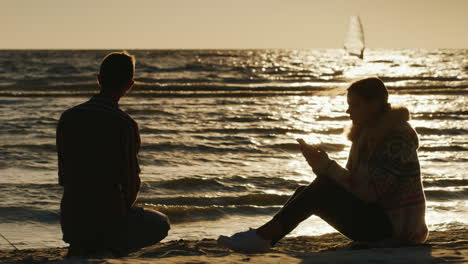 Romantic-Couple-Relaxing-On-The-Beach-At-Sunset-Woman-Enjoying-A-Telephone-A-Man-Throws-Stones-Into-