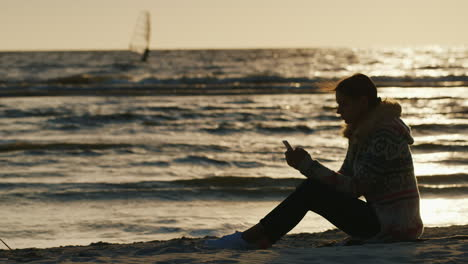 Silhouette-Of-A-Young-Woman-On-The-Sea-Berugu-Sitting-On-The-Sand-Enjoying-A-Telephone-In-The-Backgr