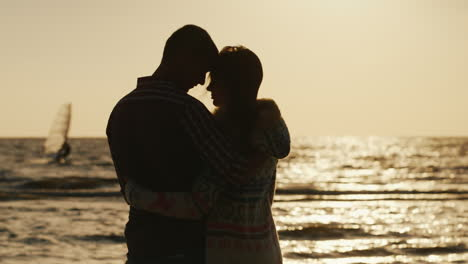 Silhouette-Of-A-Loving-Couple-Hugging-At-Sunset-Near-The-Sea-Sailboat-Floats-In-The-Distance