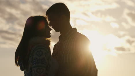 Silhouette-Of-A-Young-Couple-In-Love-On-The-Background-Of-Sky-And-Sun-Looking-At-Each-Other