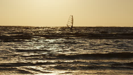 Lone-Windsurfer-Floating-On-A-Board-With-A-Sail-At-Sunset