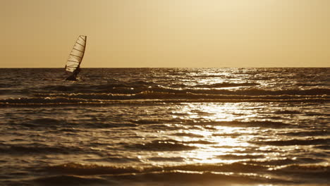 Windsurfer-Floats-On-A-Board-With-A-Sail-At-Sunset