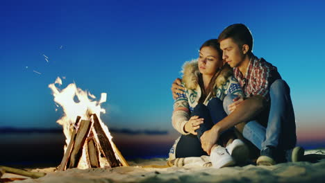 Romantic-Young-Couple-Sitting-On-The-Beach-Campfire-Hug-Admiring-The-Fire-Dreaming