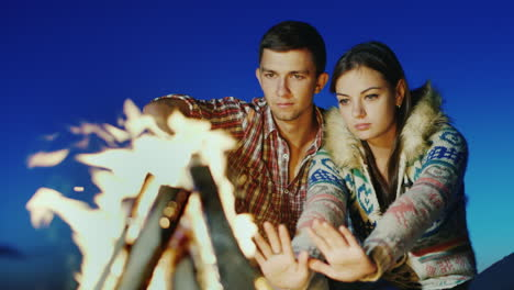 A-Loving-Young-Couple-Sitting-On-The-Beach-Campfire-Warm-Hands-By-The-Fire-Romance-And-Youth