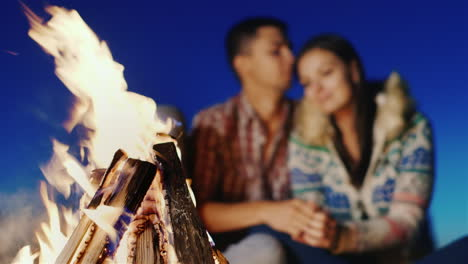 On-The-Beach-Lit-A-Fire-In-The-Background-Blurred-Young-Couple-Embracing