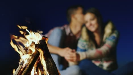 Romantic-Couple-Talking-Softly-In-The-Burning-Fire-Sharpness-On-The-Fire-A-Young-Couple-Is-Blurred