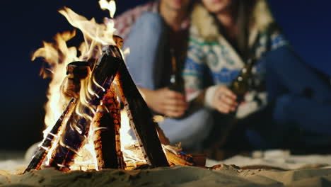 Young-People-Relaxing-By-The-Fire-In-The-Hands-Holding-A-Bottle-Of-Beer-Or-Lemonade-The-Fire-In-The-