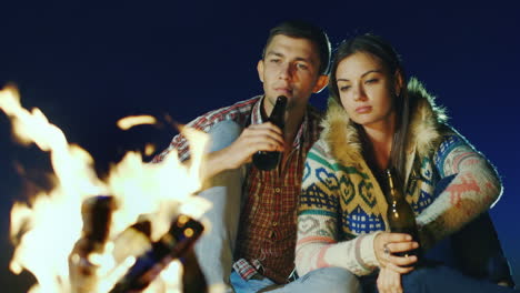 Young-Couple-Relaxing-By-The-Fire-Drinking-A-Beer-Or-A-Drink-From-The-Bottle