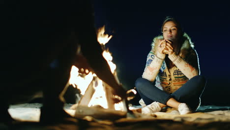 Friends-Relaxing-Around-The-Campfire-Woman-Drinking-Tea-From-A-Cup-A-Man-Chopping-Wood-With-An-Ax