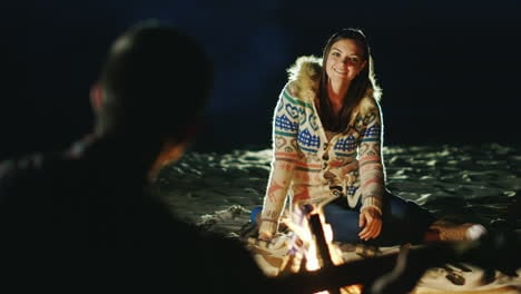 Man-Playing-Guitar-To-His-Girlfriend-Sit-Around-The-Campfire-In-The-Evening-Next-To-Each-Other