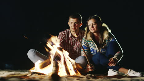 Man-And-Woman-Relaxing-Evening-Around-The-Campfire-Roast-Marshmallows-On-Sticks-Fire