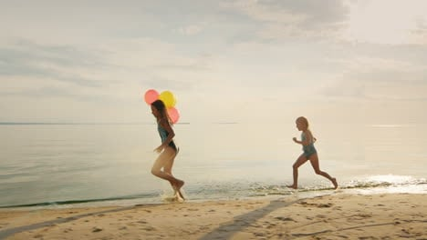 Happy-Childhood---Two-Sisters-Running-Around-Each-Other-On-The-Beach-Have-Fun-Steadicam-Slow-Motion-