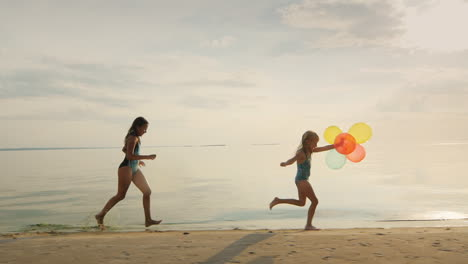 Two-Sisters-Playing-Together-On-The-Beach-One-Girl-Runs-After-Another-Holding-Balloons-Slow-Motion-S