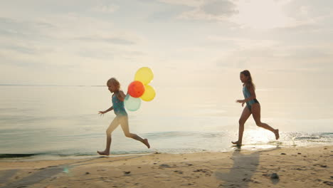 Two-Girls-Laughing-Together-Playing-On-The-Beach-Catching-Up-With-Each-Other-Holding-Balloons