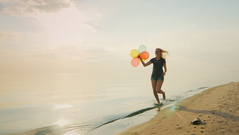 Carefree-Young-Woman-Running-On-The-Beach-Holding-Balloons-In-His-Hand-Concept---The-Ease-Freedom-Jo