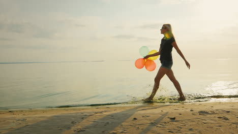 Carefree-Young-Woman-Walks-Along-The-Beach-In-The-Beautiful-Sky-Is-Holding-Balloons-Slow-Motion-Vide