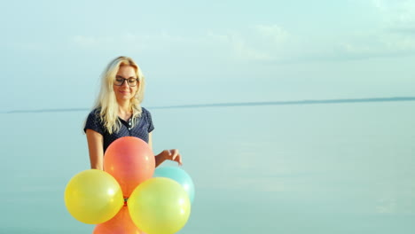 Portrait-Of-A-Young-Carefree-Woman-Walking-With-Balloons-At-The-Sea-On-A-Background-Of-Blue-Sky-Stea