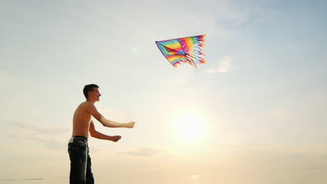 Boy-Teenager-Playing-With-A-Kite-Against-The-Background-Of-Blue-Sky-Side-View