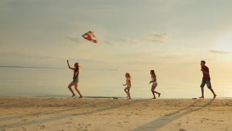 Group-Of-Children-Playing-With-Adults-Let-Them-Into-The-Sky-Kite-Fun-Running-On-The-Beach