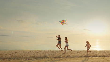 Mother-With-Two-Daughters-Playing-On-The-Beach-With-A-Kite-The-Fun-Run-Together-Happy-Childhood