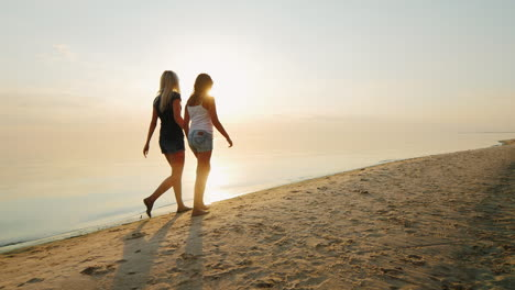 Mum-With-A-Daughter-8-Years-Old-Walking-On-The-Beach-Together-Back-View
