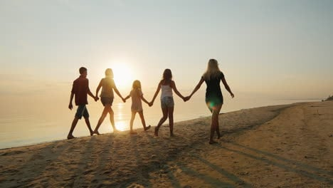 Group-Of-Children-Of-Different-Ages-With-Adults-Are-On-The-Beach-At-Sunset-Holding-Hands-Rear-View-S