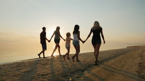 The-Company-Of-Children-And-Adults-Are-Having-Fun-On-The-Beach-Holding-Hands-Rear-View-At-Sunset