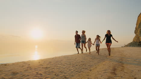 Group-Of-Carefree-Children-Of-Different-Ages-And-Adults-Have-Fun-Running-On-The-Beach-At-Sunset