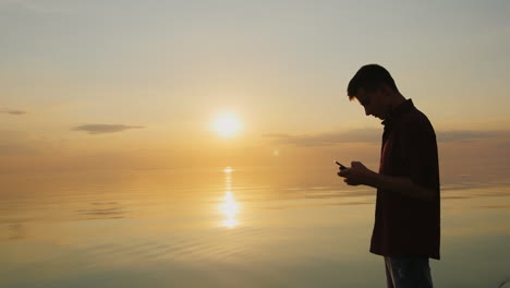 A-Teenager-Of-15-Years-Enjoys-The-Phone-It-Should-At-Sunset-On-The-Background-Of-A-Calm-Sea