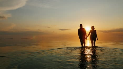 A-Man-And-A-Woman-Go-To-The-Sea-At-Sunset-Holding-Hands-Silhouettes-In-The-Light-Of-The-Setting-Sun