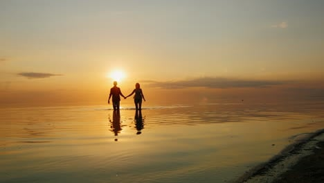 Man-And-Woman-Running-Through-The-Water-To-The-Camera-Fly-Spray-At-Sunset